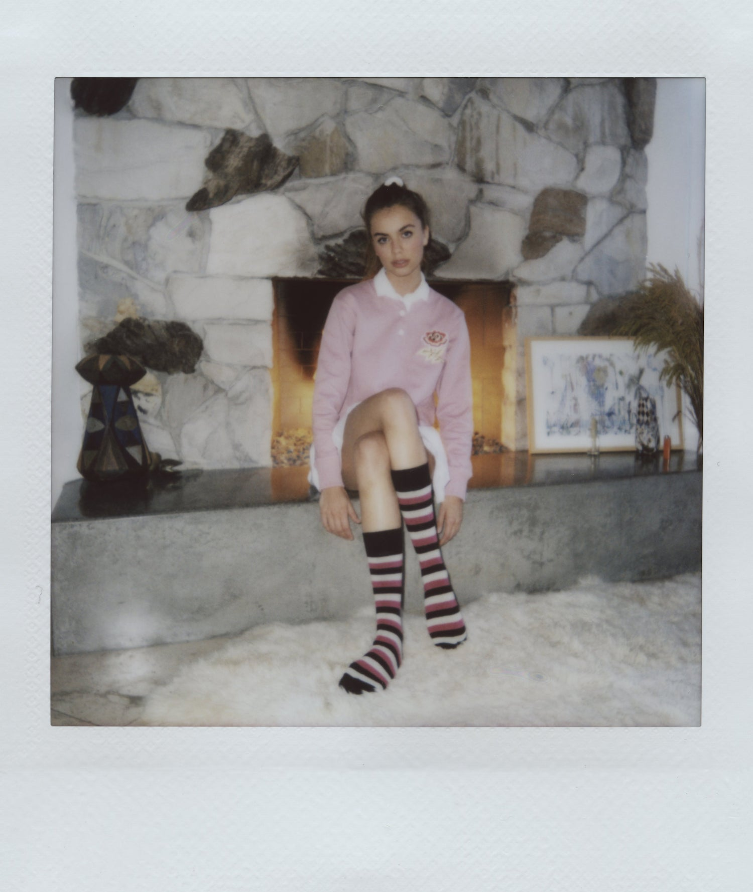 Polaroid of Alex Lee-Aillón sitting by a fireplace.