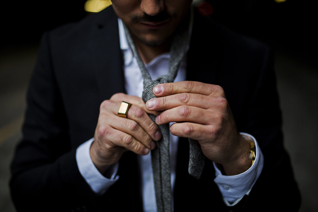 Man With Gold Signet Ring Tying A Tie