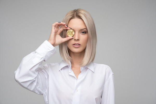 Blonde Woman in White Shirt Holding a Bitcoin on Her Eye
