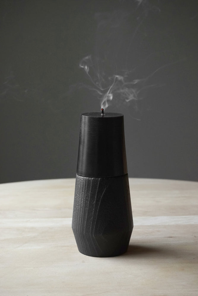 Black beeswax pillar candle with a black wooden base.