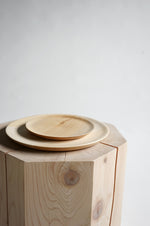 Stacked maple wooden plates on top of a wood stool.