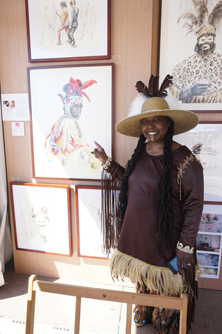 Big Queen Rukiya Brown poses with a portrait of her by Annie Moran