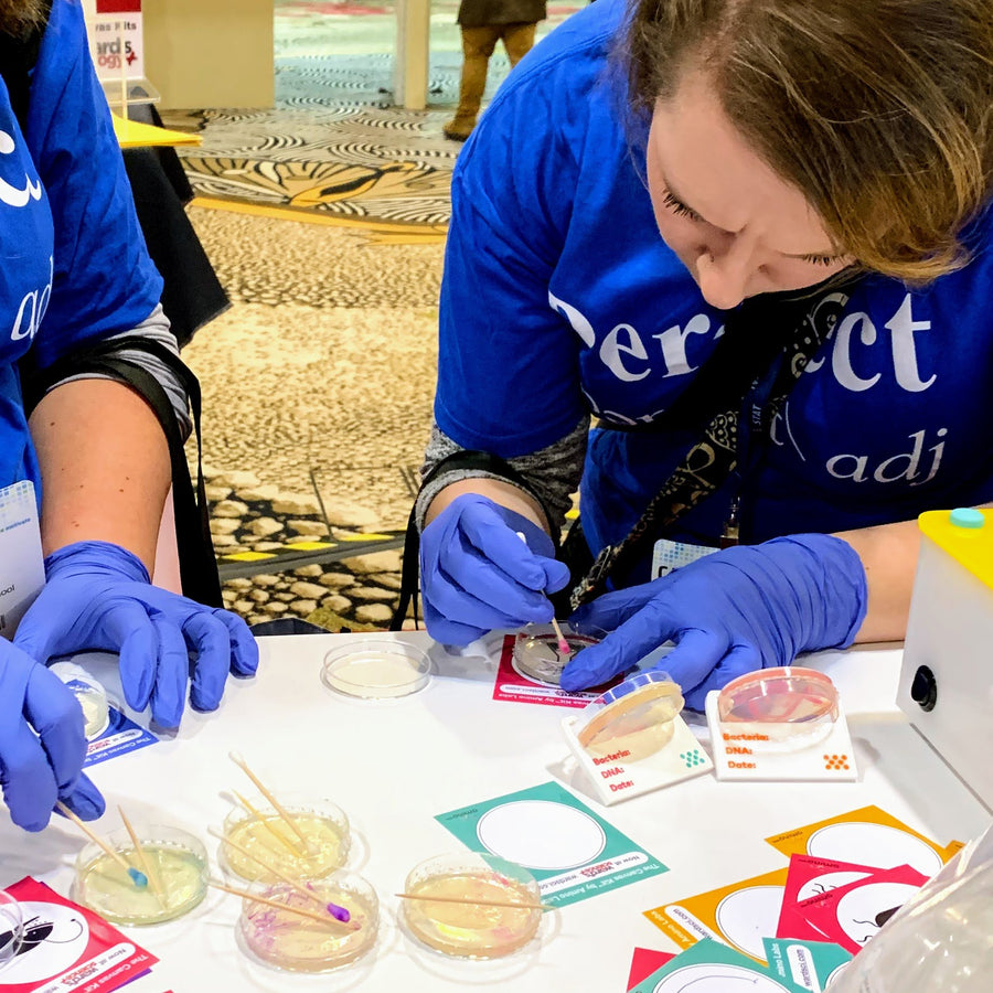 students holding a petri dish of bacteria art made with Amino Labs' Zero to Genetic Engineering hero starter pack for  middle school science, biology, genetics, high school science, biology, genetics, NGSS.  Learn what is DNA, what is a gene, cell theory, genetic engineering, bioart, biotechnology, biohacking and genetic engineering with the world's first biohacking and biotechnology STEM beginner's book and starter pack of science project kits, biotechnology project kits