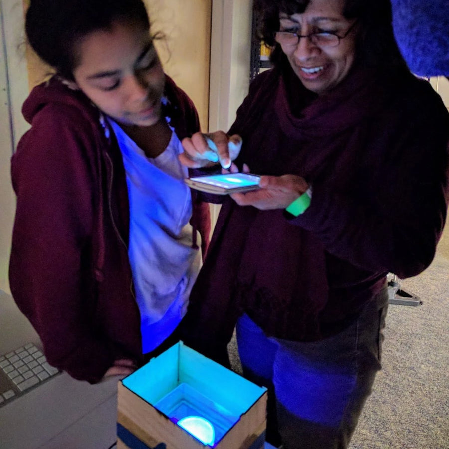 mother and daughter taking a photo of glowing bacteria during a Genetic Engineering DIY biohacking workshop by Amino labs STEM biotechnology kits and school laboratory equipment / home laboratory equipment / biohacking laboratory equipment