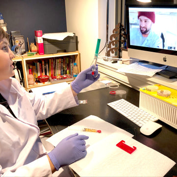 young student in lab coat showing a syringe to a scientist during a Genetic Engineering DIY biohacking virtual lessons by Amino labs STEM biotechnology kits and school laboratory equipment / home laboratory equipment / biohacking laboratory equipment