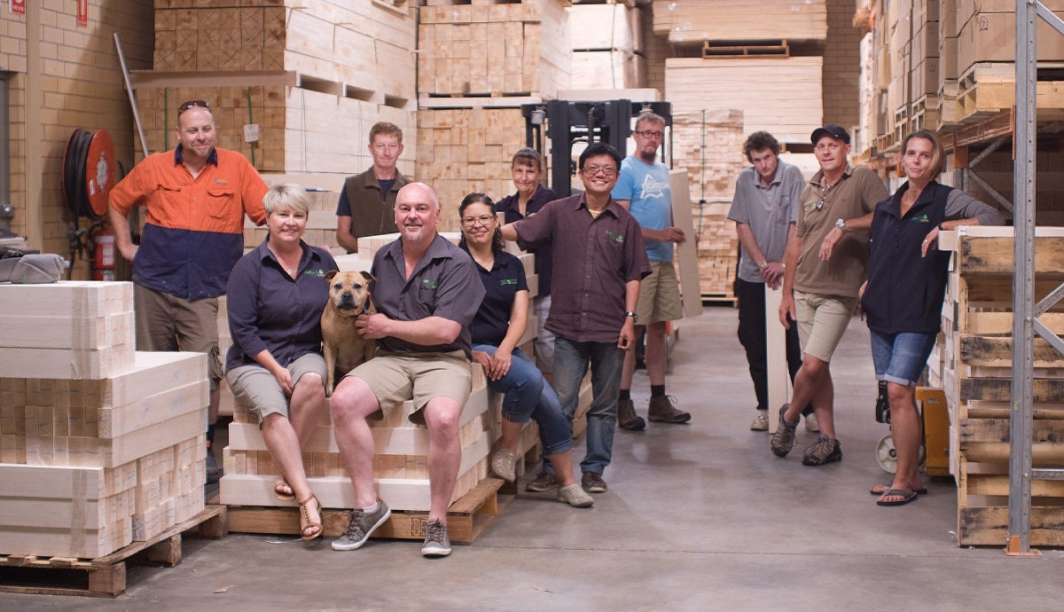 A happy team of 11 Balsa Central employees and a dog in their warehouse