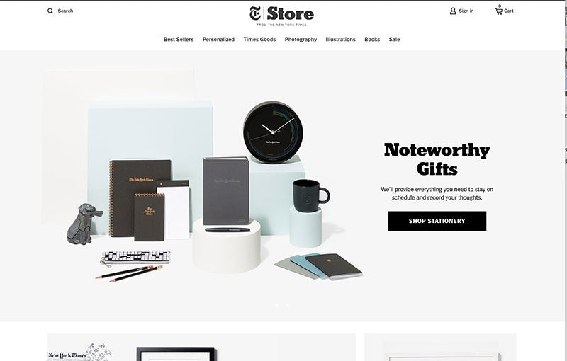 New york times store header with elegant stationery, a clock and a cta to shop for noteworthy gifts