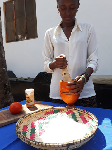 Kwege grinding the spices for a Taste of Tanzania Cooking Experience