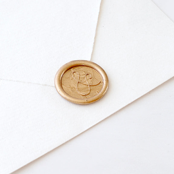Chic gold ampersand wax seal on white envelope