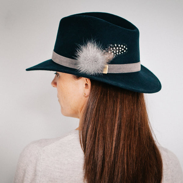 navy blue wool felt fedora with grey band and grey fur pom pom and black and white guinea fowl feather
