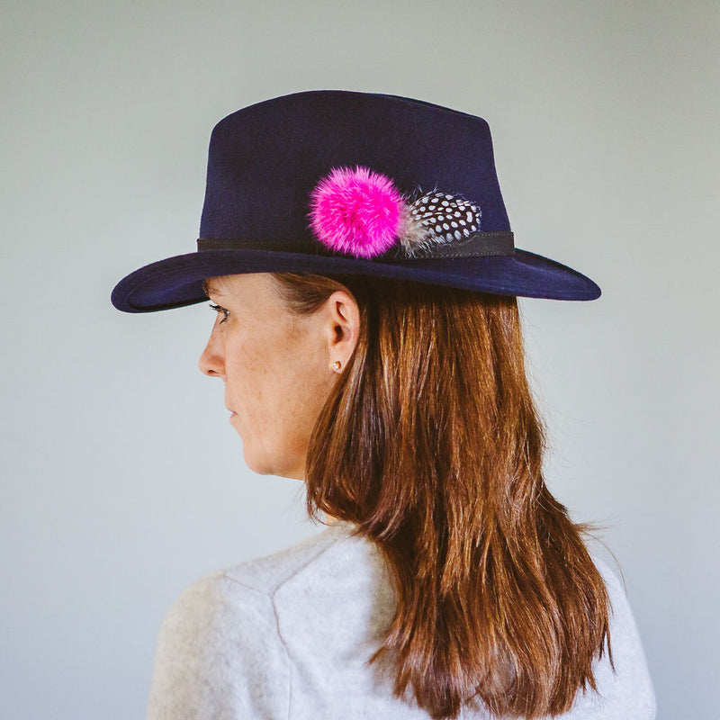 navy blue wool felt fedora with black leather band fuchsia pink fur pom pom and black and white guinea fowl feather