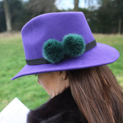 purple wool felt fedora with black band and two dark green fur pom poms