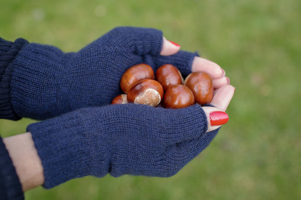 100% cashmere navy fingerless gloves holding a handful of conkers
