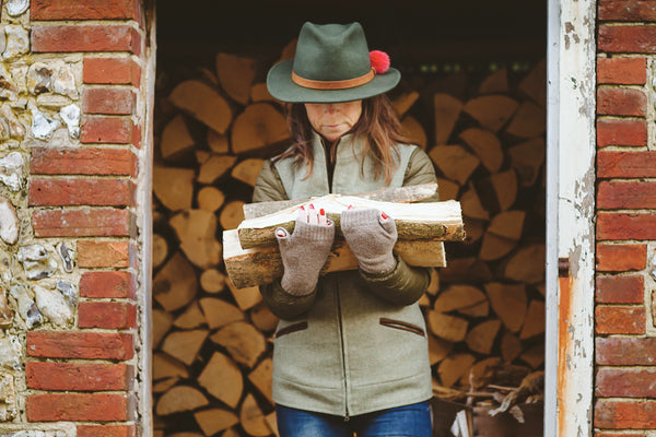 100% cashmere otter beige wristwarmers holding pile of logs and dark green fedora with red pom pom