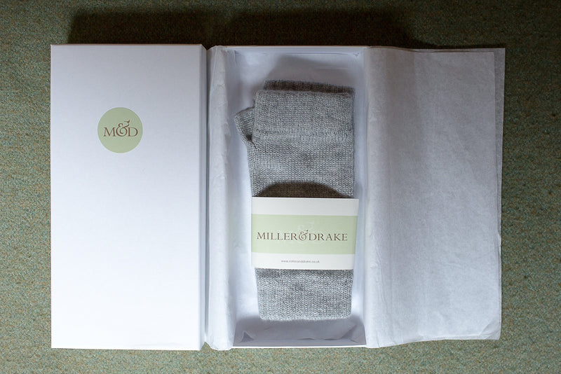 100% cashmere grey wristwarmers wrapped in tissue paper in a luxury white gift box