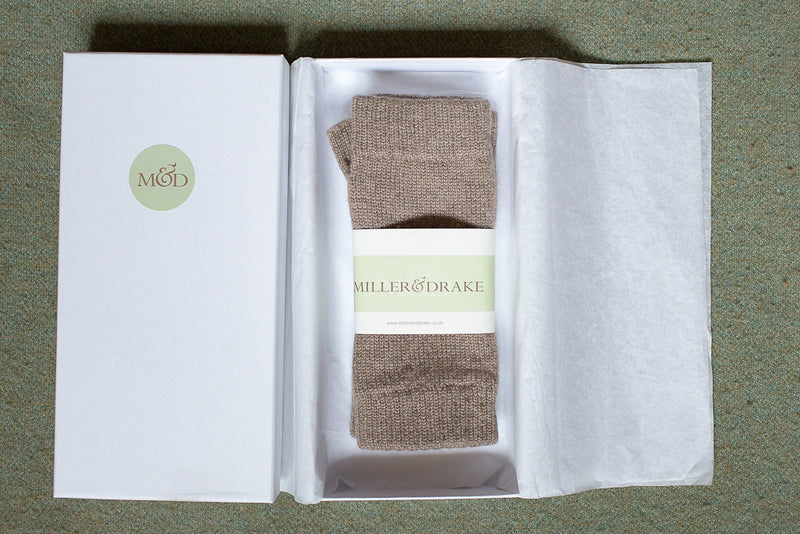 100% cashmere otter beige wristwarmers wrapped in tissue paper in a luxury white gift box