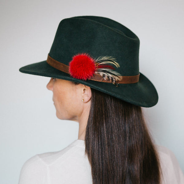 dark green wool felt fedora with tan leather band red fur pom pom and yellow black and brown feathers