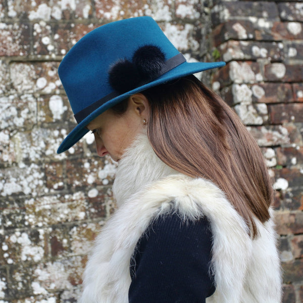 teal wool felt fedora with black band and two black fur pom poms