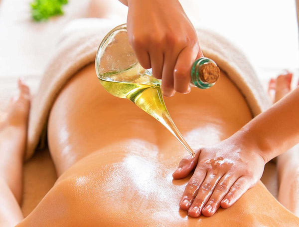 Ayurvedic massage with oil being poured onto the back