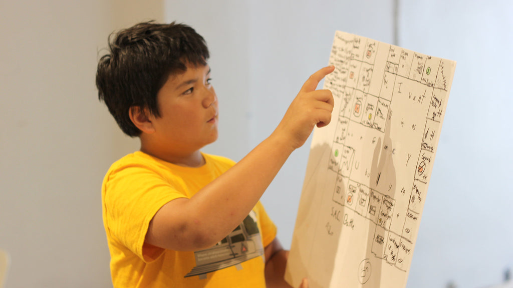 Kid explaining his board game design at Little Robot Friends camp
