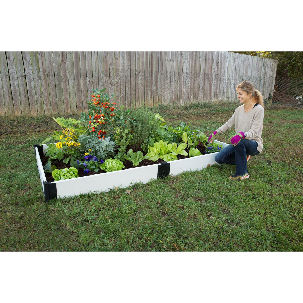 Raised Garden Bed - Composite Classic White Rectangle. Shown on lawn woman kneeling next to bed filled with plants