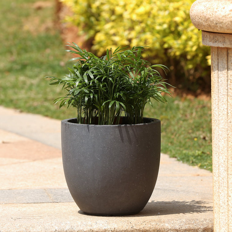 Round Stone Finish Planter Dark Grey on Patio with flowers planted