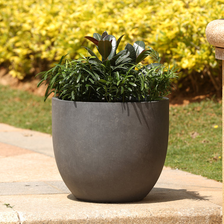Garden Planter - Round, Stone Finish in Dark Grey Medium shown on patio with green plants inside