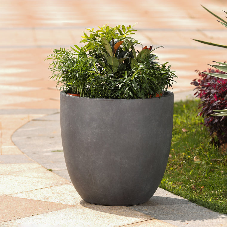 Garden Planter - Round Stone Finish in Dark Grey Large shown on patio with green plant inside