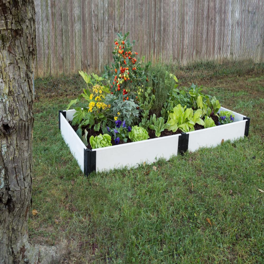 Raised Garden Bed - Composite Classic White Rectangle. Shown on lawn bed filled with plants