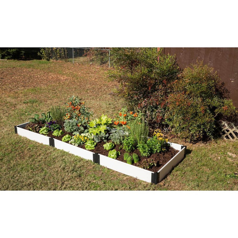 Composite Raised Garden Bed Kit. Composite Classic White. Top overview shows bed on lawn with plants in bed