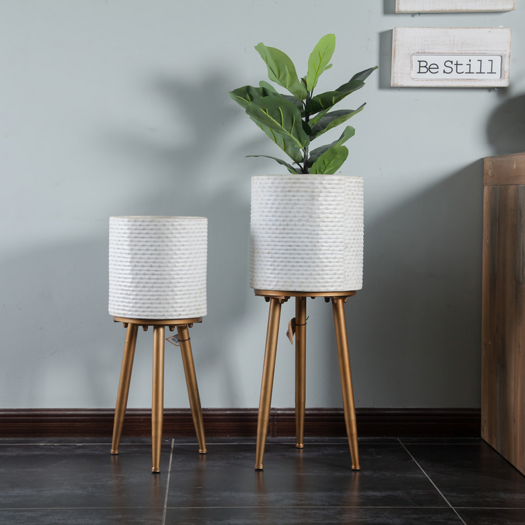 2 white planters on gold tripod base taller one with plant in planter in living area