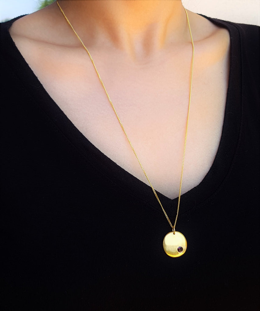 Gold brushed disc neckalce with garnet