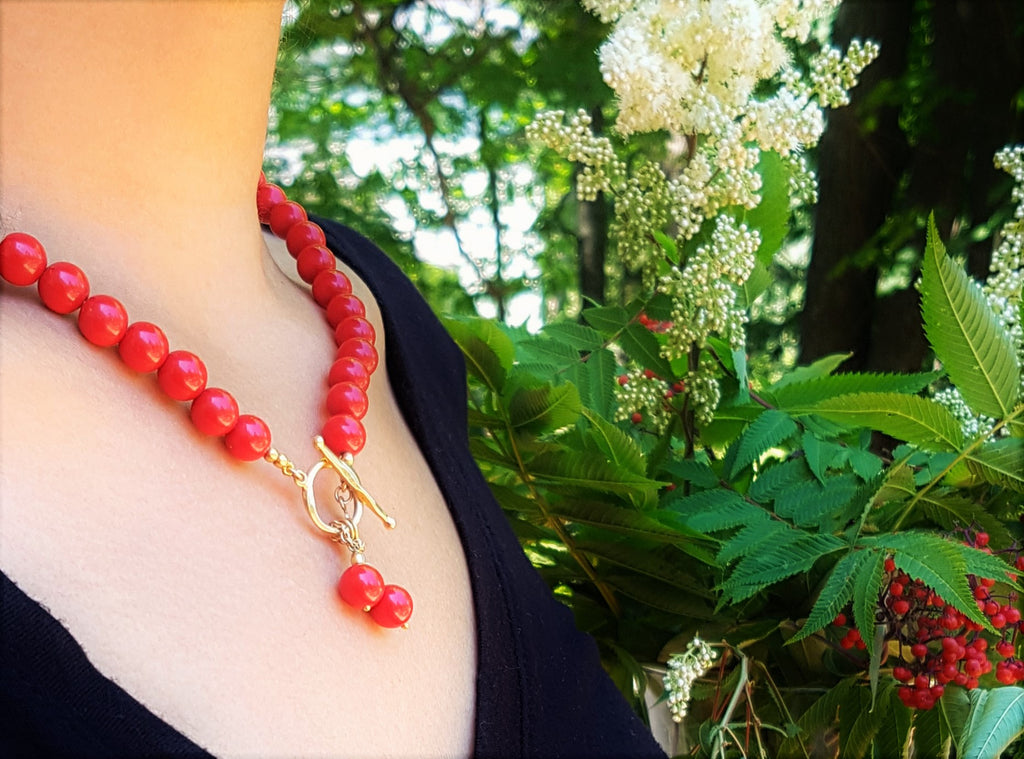 Model wearing the red coral bead necklace with gold toggle clasp
