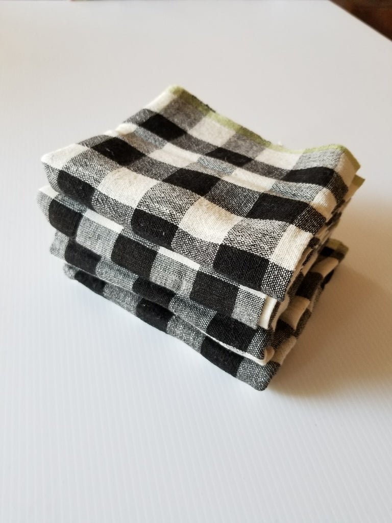 set of 4 chequered black and ivory handwoven napkins with a green edge