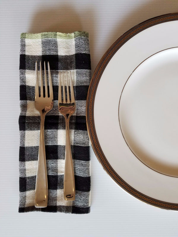 chequered black and ivory handwoven napkins with a green edge displayed with table setting