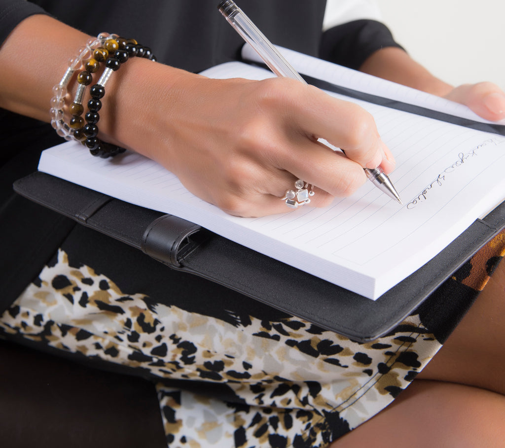 close up woman's hand writing with pen on notebook wearing gemstone bracelets and silver stacking open rings