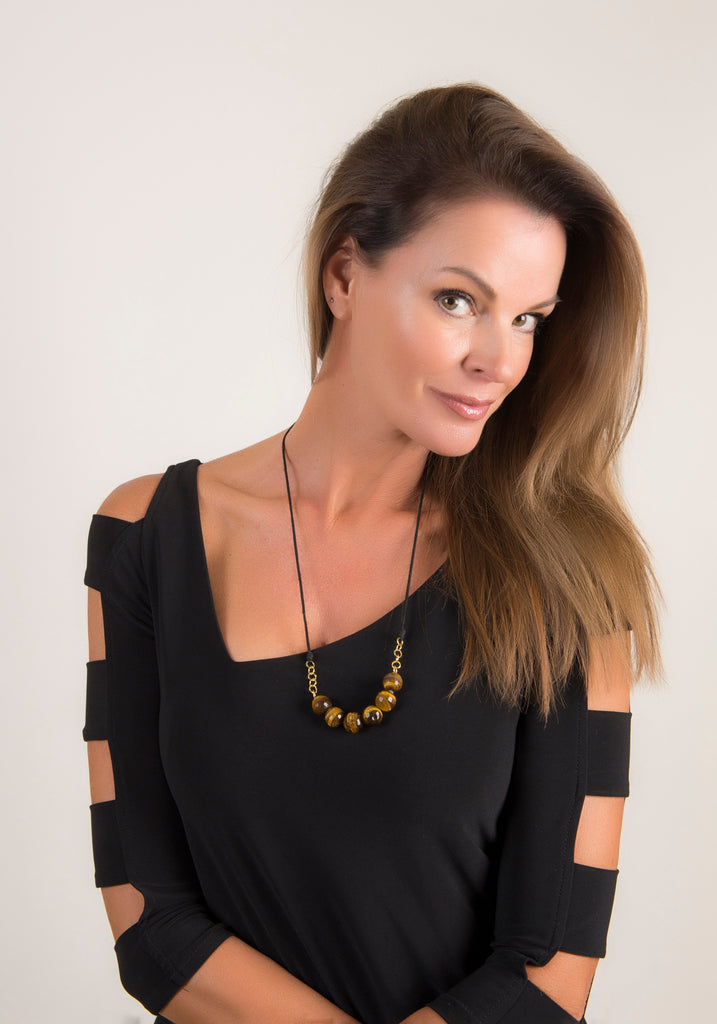 female model wearing necklace with round faceted tiger's eye beads hanging in the middle of black rope