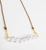 Shining cut crystal beads centred on a brown rope necklace with gold detailing