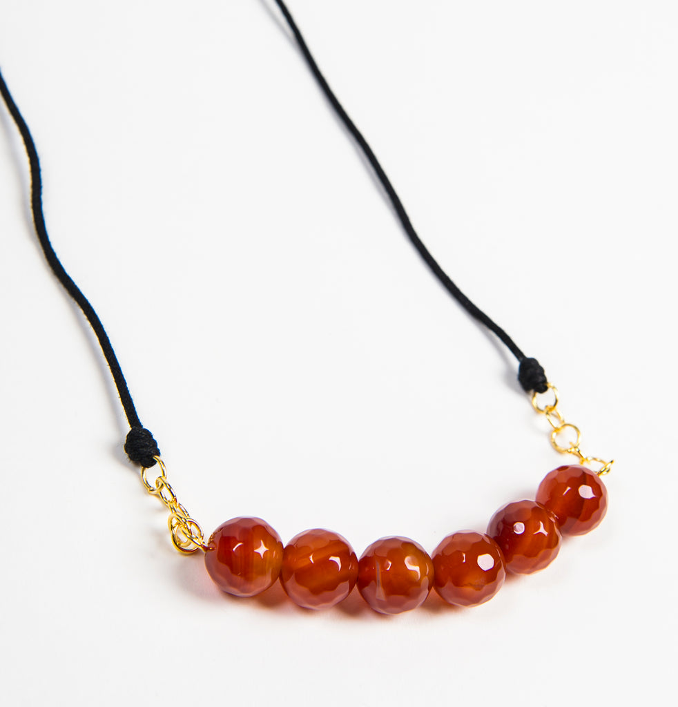 ethically made fashion jewelry necklace with black string, gold links and carved carnelian