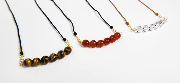 three necklaces with six semi-precious stone beads on the end of an adjustable black rope