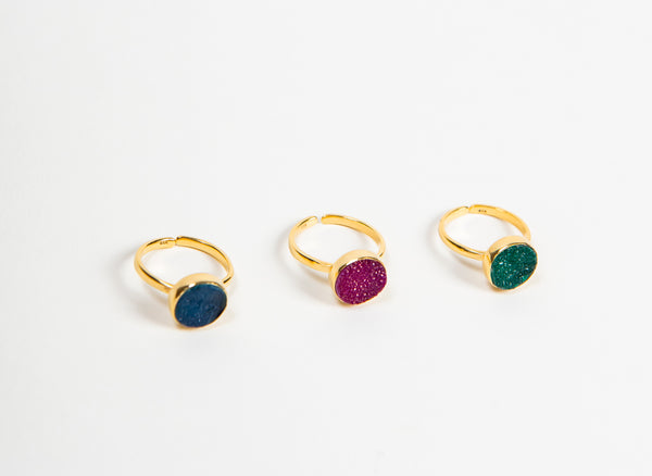 three adjustable gold rings with different coloured druzy stone settings on white background