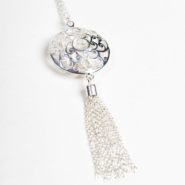Close up of sterling silver filigree pendant with handing tassel on long necklace