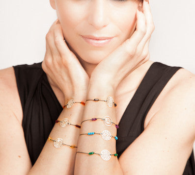 A collection of 7 silk chakra bracelets on model by thank you india