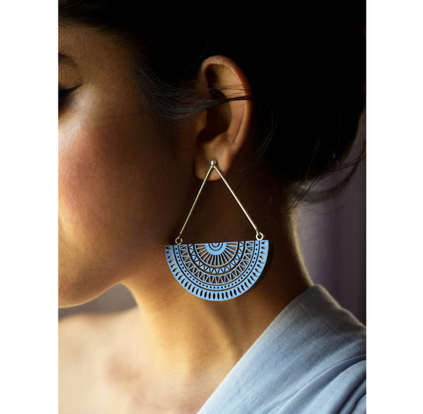close up of hanging indigo chandratithi earrings on female model