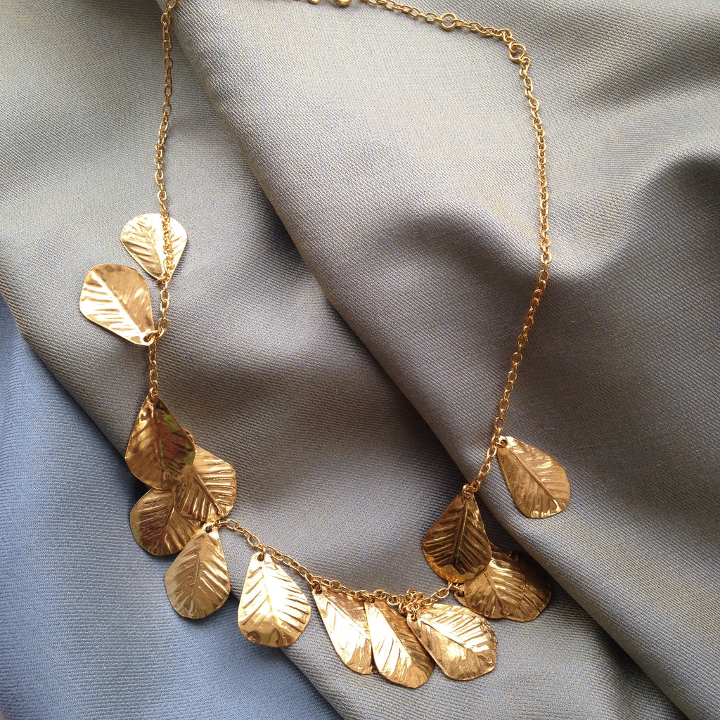gold fig leaf necklace placed on silk by Thank You India