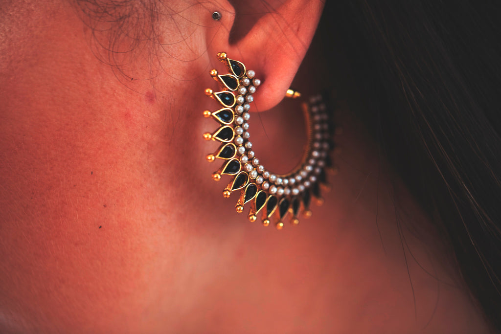 Model wearing the Black and gold bollywood style stud earrings with posts and spike detail
