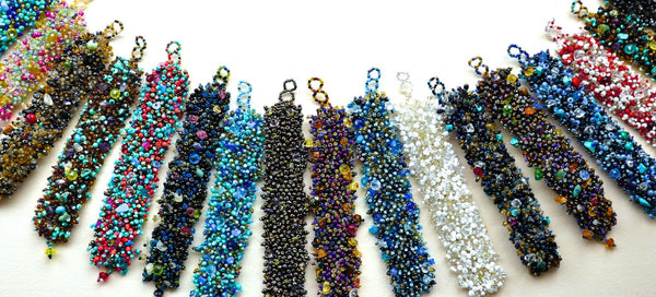 all colours of large Spectacular Bead Bracelets in arc on white background