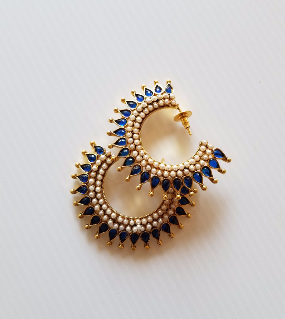 Pair of circular stud earrings with gold tone, blue stone crystals and pearl-style detail
