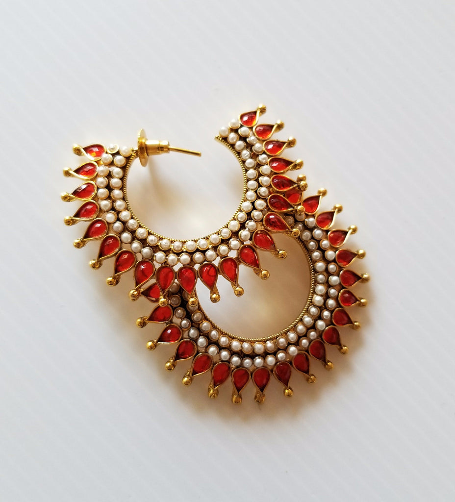 red studded earring with pearl-style detailing and gold toned metal