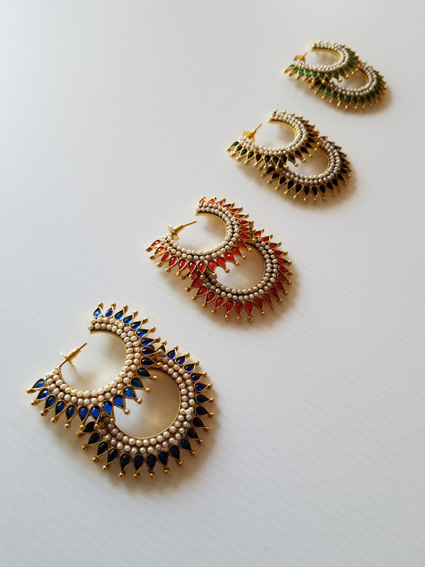 four pairs of Unique studded earrings in gold and black, red, blue and green